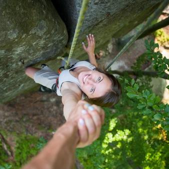 岩が多い壁に女性のクライマーを手で押しロッククライマー