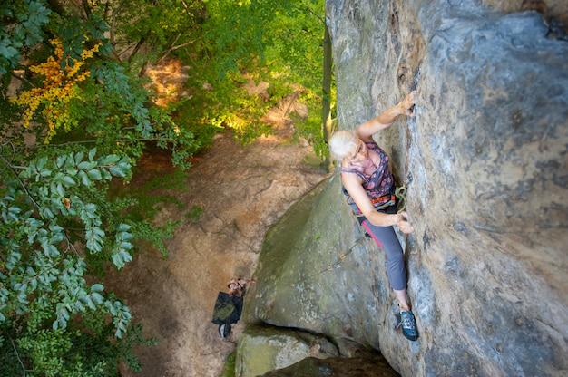 年上の女性ロック・クライマーは岩が多い壁に登っています