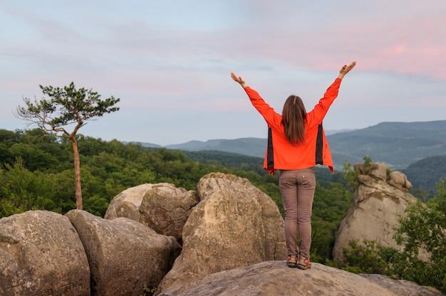 Женщина турист на большой скале на вершине горы