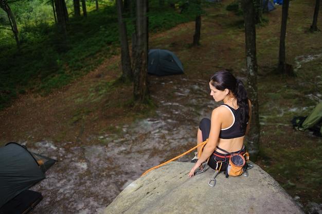 森の中の大きな自然の巨石の上に座って女性登山家