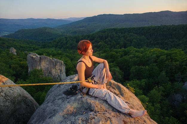 Девушка альпинист на вершине горы на большой высоте в вечернее время
