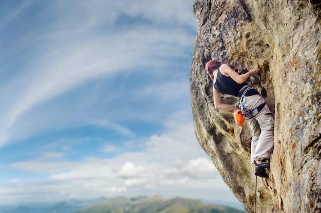 急な張り出した岩崖の上の女性ロック・クライマー