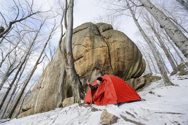 男性ハイカーは山の中で彼のほぼ赤いテント