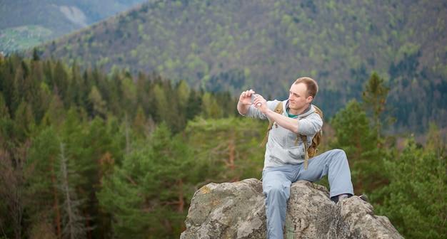 岩の頂上に茶色のバックパックを持つ男性の登山家