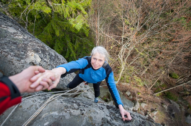 男性のロッククライマーは登山者の女性を助けています