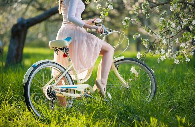 Красивый женский велосипедист с ретро велосипедом в саде весны