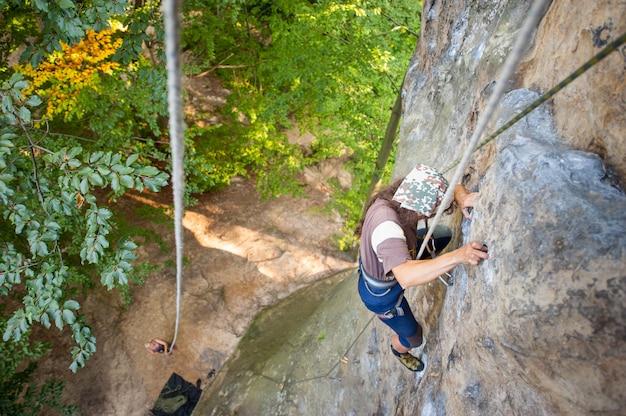 女性ロック・クライマーは岩が多い壁に登っています