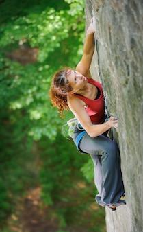 険しい岩をロープで登る美しい女性のクライマー