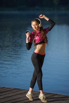 屋外音楽を楽しむイヤホンを持つ女性ランナー