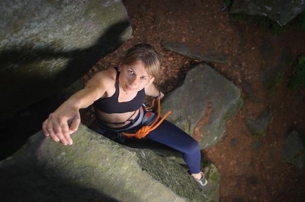 岩が多い壁にロープで登山の女性クライマー