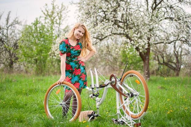 春の庭でビンテージ白い自転車を持つ女性サイクリスト