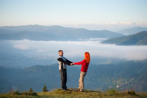 手を繋いでいると丘の上にお互いに直面しているペア