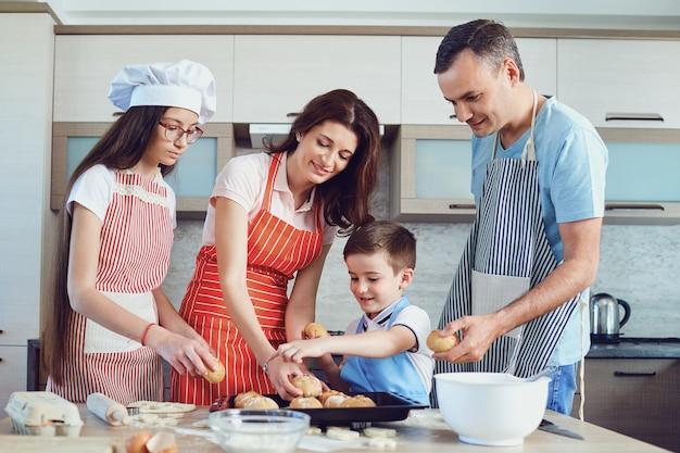 幸せな家族は台所で焼く準備をします。