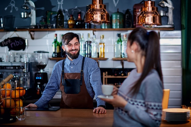 Бармен, бариста и клиент в кафе-баре-ресторане