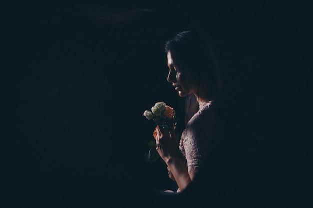 花を持つ女性のプロフィール。女の子はバラを盗聴します。暗闇の中で女性のシルエット
