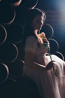 金属パイプの間で花の花束と光のドレスで美しい少女