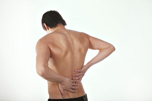 背中の痛み:彼の痛みの胴体を保持している白い背景の上の男