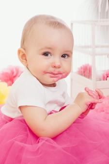 少女は彼女の手でケーキを食べる。その赤ちゃんは食べ物で覆われていた。誕生日会