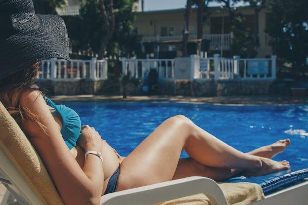 妊娠中の女性がプールサイドのサンラウンジャーで日光浴