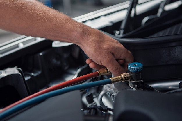 車の修理とクリーニングのコンセプト-車のエンジンのクローズアップ、ボンネットの下の部品を拭く