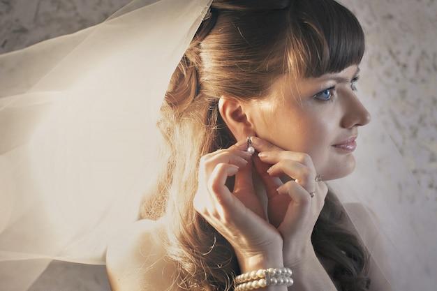 花嫁は宝石を試着します。モデルはイヤリングを示しています。ラインストーン付きフレンチマニキュア