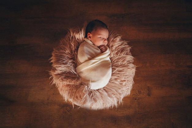 Новорожденный ребенок, завернутый в одеяло, спать в корзине. концепция детства, здравоохранение, эко