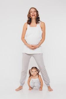 Мама и дочь, развлекаясь на белом фоне. беременная женщина и ребенок играют вместе. концепция детства, здравоохранение, эко