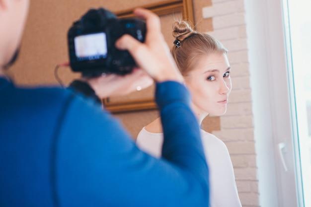 写真家はスタジオで美しいモデルを撮影します。女の子は服をアドバタイズします。写真およびビデオ広告