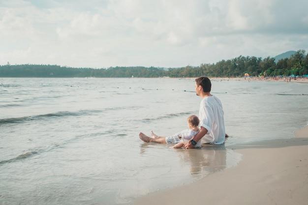 サングラスのお父さんはビーチの背景に彼の腕の中で赤ちゃんを保持します。