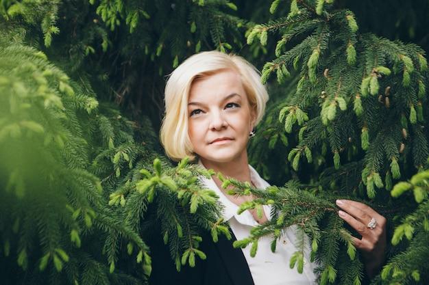路上での作業、昼休み-白い短い髪の女性のおしゃれなスタイリッシュな肖像画。木の中で公園を歩いて実業家。