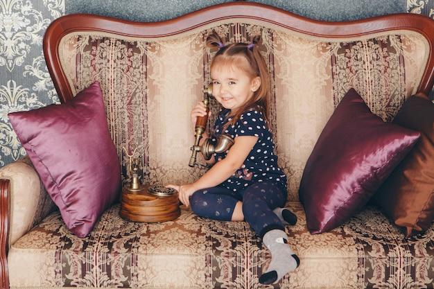 Маленькая девочка сидит на диване и разговаривает по старому телефону