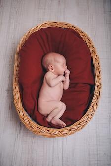 Новорожденный ребенок, завернутый в одеяло, спит в корзине