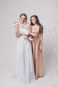 すべての年齢の女性のための結婚式のファッション。白の長いイブニングドレスの女性のグループ