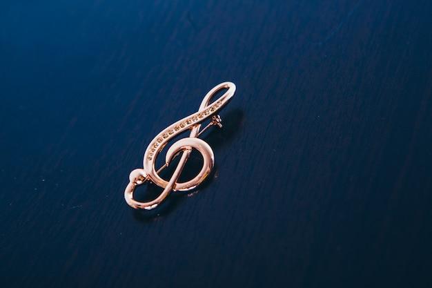 暗闇の中で金のバイオリン。装飾、ブローチ。 。音楽記号、孤立したオブジェクト、ジュエリー作品、ジュエリー