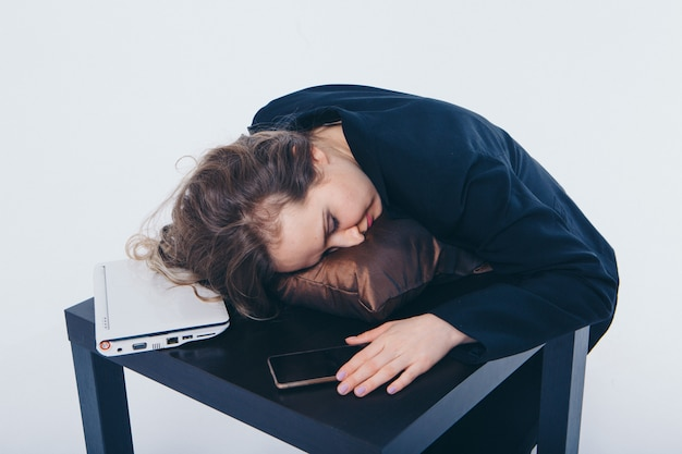 Деловая женщина в деловом костюме и с телефоном и ноутбуком, спать на столе