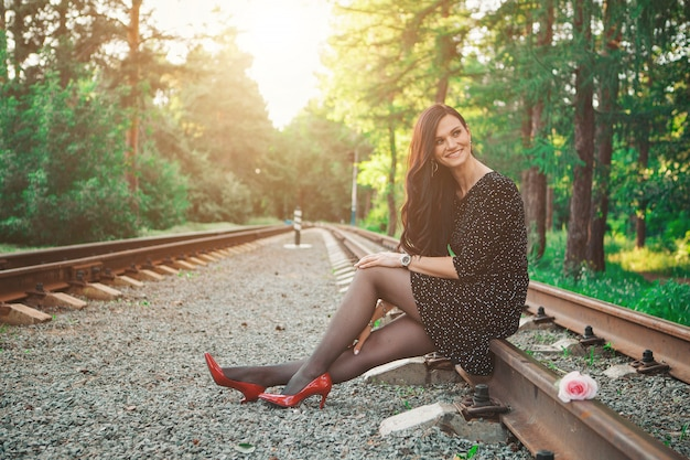 黒のドレスと赤い靴の美しいブルネットはレールの上に座っています
