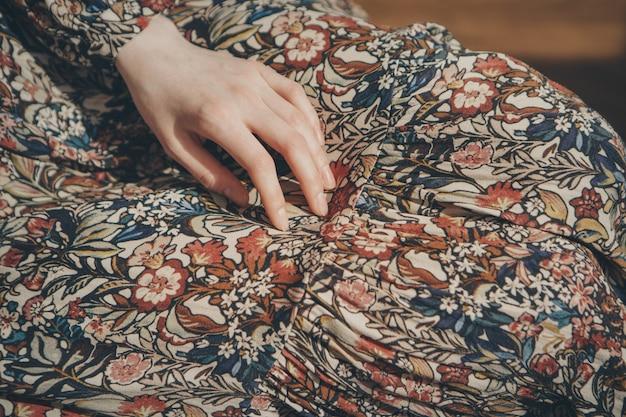 女性のファッションの広告:ドレス、スーツ。女性の腕と袖のクローズアップ。衣類、縫い目、ステッチの飾り