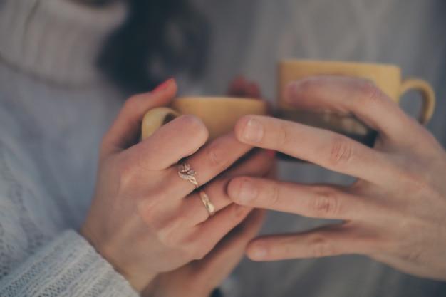 男性、女性の手とカップのクローズアップ。ランチやコーヒー、お茶、恋のカップルのために休憩。バレンタイン・デー