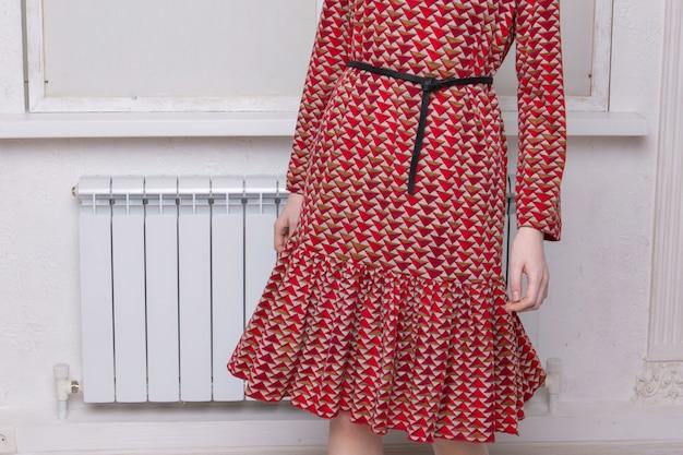 女性のファッションの広告:赤いドレス、スーツ。女性の手、ストラップとスリーブのクローズアップ。衣類、縫い目、ステッチの飾り