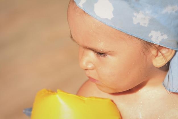 肘掛けの少女と休暇中に水泳帽の肖像画。水泳、休暇、水処理のための機器の概念
