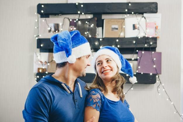 Мужчина и женщина в новогодних голубых шапках обнимаются.