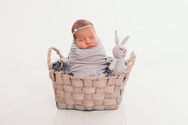 Маленький ребенок в корзине с игрушкой белого кролика. детство, здравоохранение, эко, подарок, животное. изолированные на белом фоне