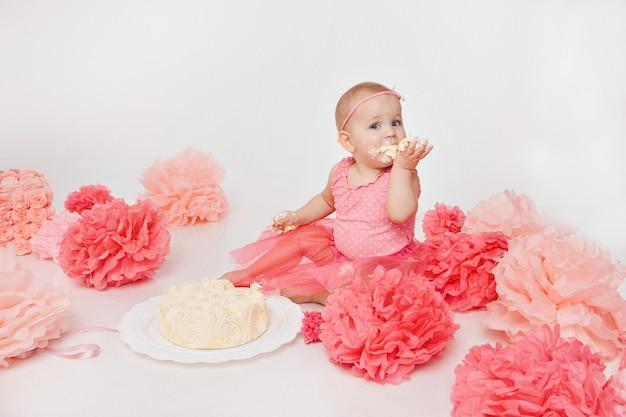 Празднование дня рождения: маленькая девочка ест торт своими руками на белом. ребенок покрыт едой. разрушенная сладость.
