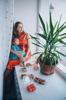 青い目の白人女性と寿司を食べる伝統的なチャイナドレスの女の子。日本文化の金髪と子供。健康食品、東洋料理のコンセプト