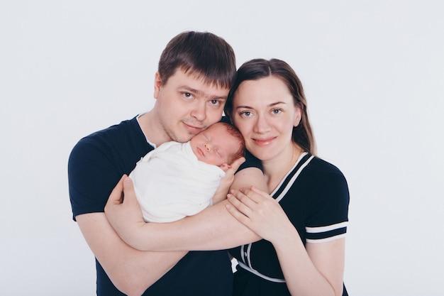 健康的なライフスタイル、子供の保護、ショッピング-母親と父親の腕の中で赤ちゃん。女と男が子供を抱いて