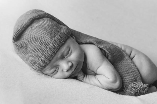 生まれたばかりの赤ちゃんは白のクリスマス帽子で眠る。健康的なライフスタイル、体外受精、クリスマス、年末年始、おもちゃ