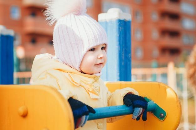 小さな女の子が遊び場で遊んで