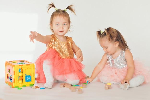 白い背景の上の床で遊ぶ二人の少女
