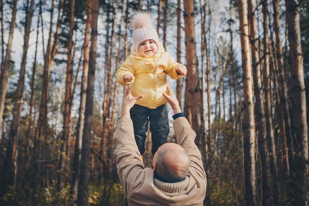 暖かいスーツを着たお父さんと小さな子供が森の中を歩きます。秋の公園。子供のファッション、アクセサリー、アウトドアウォークのコンセプト