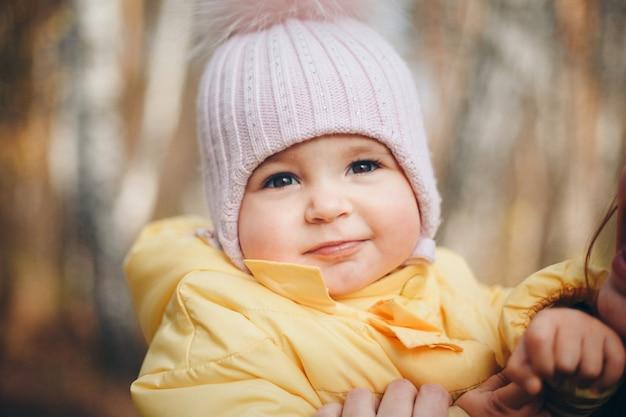 Маленькая девочка в теплой шапке на голове улыбнулась. концепция детства, здоровья, эко, холодного времени
